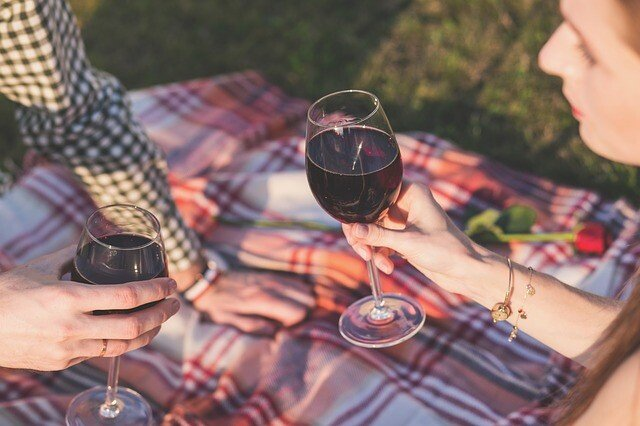 two people with wine at a picnic
